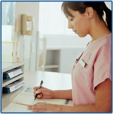 medical assistant is making notes in a patient card. She wears a nice pink shirt, and we can see the medical practice in the background