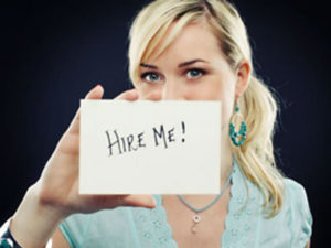 """young lady wants to get hired, showing a paper with """"hire me"""" words written on it, in capital letters."""