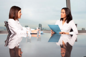 Two women in white clothes talk in the office. One of them is a physician, another one a job candidate.